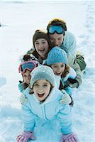 Young friends dressed in ski clothes, sitting in snow, portrait Stock Photo - Premium Royalty-Freenull, Code: 632-01380760