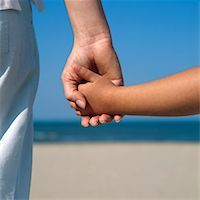 Woman and girl (6-8) on beach holding hands, close up Stock Photo - Premium Royalty-Freen