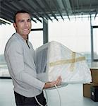 Man carrying computer monitor covered in bubble wrap, portrait Stock Photo - Premium Royalty-Free, Artist: Blend Images, Code: 613-01385604