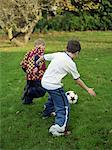 Two brothers playing football in garden, rear view Stock Photo - Premium Royalty-Freenull, Code: 613-01387479