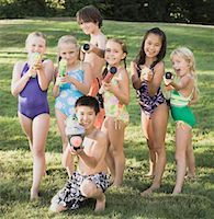 Seven children (7-12) holding squirt guns outdoors, portrait Stock Photo - Premium Royalty-Freenull, Code: 613-01394630