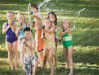 Seven children (7-12) holding squirt guns outdoors, portrait Stock Photo - Premium Royalty-Freenull, Code: 613-01394631