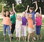 Seven children (7-12) cheering, arms raised, portrait Stock Photo - Premium Royalty-Freenull, Code: 613-01394634