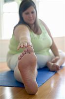 Woman stretching, reaching toes (focus on foreground) Stock Photo - Premium Royalty-Freenull, Code: 613-01395383