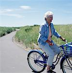 Senior woman riding bicycle on coastal path Stock Photo - Premium Royalty-Freenull, Code: 613-01401433