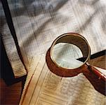 Magnifying glass on top of newspaper stock reports Stock Photo - Premium Royalty-Free, Artist: Glowimages               , Code: 618-01417597