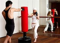 student fighting - Young man and woman hitting the punching bag Stock Photo - Premium Royalty-Freenull, Code: 644-01436528