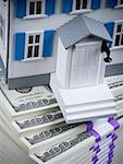 Toy house on stack of hundred dollar bills Stock Photo - Premium Royalty-Free, Artist: AWL Images, Code: 640-01458623