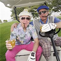Two mature men sitting in the back of a golf cart, toasting Stock Photo - Premium Royalty-Freenull, Code: 613-01470485