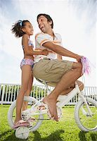 Father and daughter on bicycle with streamers smiling Stock Photo - Premium Royalty-Freenull, Code: 635-01488982
