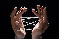 Close-up of a person's hands playing cats cradle with a rubber band Stock Photo - Premium Royalty-Freenull, Code: 630-01490518
