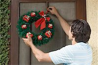Rear view of a young man hanging wreath on a door Stock Photo - Premium Royalty-Freenull, Code: 630-01491223
