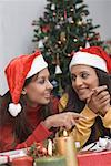 Two young women wearing Santa hats and looking at each other Stock Photo - Premium Royalty-Freenull, Code: 630-01491413