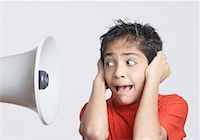 preteen open mouth - Close-up of a boy covering his ears with his hands and looking at a megaphone Stock Photo - Premium Royalty-Freenull, Code: 630-01491544