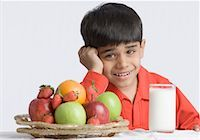 Portrait of a boy making a face in front of a glass of milk and a basket of fruits Stock Photo - Premium Royalty-Freenull, Code: 630-01491809