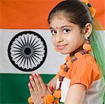 Portrait of a girl in a prayer position in front of an Indian flag