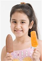 Portrait of a girl holding two ice creams Stock Photo - Premium Royalty-Freenull, Code: 630-01492104