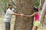 Side profile of a young couple running around a tree Stock Photo - Premium Royalty-Freenull, Code: 630-01493022