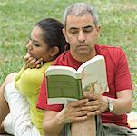 Close-up of a mid adult man reading a book with a mid adult woman sitting behind him Stock Photo - Premium Royalty-Freenull, Code: 630-01493025