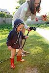 Mother and Son Watering Grass    Stock Photo - Premium Rights-Managed, Artist: Mark Peter Drolet, Code: 700-01519657
