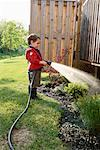Boy Watering Garden    Stock Photo - Premium Rights-Managed, Artist: Mark Peter Drolet, Code: 700-01519662