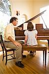 Man watching girl playing piano Stock Photo - Premium Royalty-Free, Artist: Bruce Fleming, Code: 621-01519909