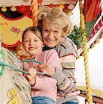 Grandmother on carousel with granddaughter (7-9) smiling, portrait Stock Photo - Premium Royalty-Freenull, Code: 613-01522792
