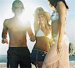 Three young friends dancing on beach, smiling (sun flare)