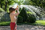 Boy (2-4) playing with garden hose and sprayer in yard, rear view Stock Photo - Premium Royalty-Freenull, Code: 613-01526994