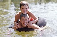 Two brothers (11-14) on inflatable ring in lake, smiling, portrait Stock Photo - Premium Royalty-Freenull, Code: 613-01527149