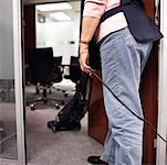 Senior woman standing in doorway hoovering office Stock Photo - Premium Royalty-Free, Artist: ableimages, Code: 613-01530392