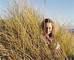 Girl (12-14) in long grass on beach, smiling, portrait Stock Photo - Premium Royalty-Free, Artist: Aurora Photos            , Code: 613-01531808