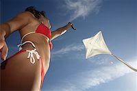 Woman in bikini flying kite, low angle view Stock Photo - Premium Royalty-Freenull, Code: 613-01532144