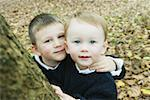 Two brothers (2-5) beside tree, autumn, portrait, elevated view