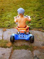 Boy (2-4) riding on toy car, rear view Stock Photo - Premium Royalty-Freenull, Code: 613-01534260