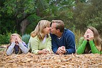 Couple kissing while kids cover eyes Stock Photo - Premium Royalty-Freenull, Code: 621-01554092