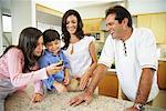 Family in kitchen, Looking at Cell Phone