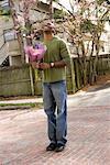 Smiling young man standing on street holding  bouquet of flowers Stock Photo - Premium Royalty-Free, Artist: Transtock, Code: 638-01583322