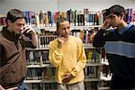Three teenage boys talking on cell phones in a library Stock Photo - Premium Royalty-Free, Artist: Brian Pieters, Code: 638-01584770