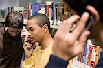 Close-up view of three teenage boys talking on cell phones in a library Stock Photo - Premium Royalty-Free, Artist: Brian Pieters, Code: 638-01584772