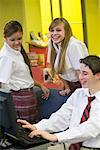 Teenage boy in school uniform using computer while girls watch Stock Photo - Premium Royalty-Free, Artist: Brian Pieters, Code: 638-01584776
