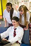 Teenage boy in school uniform using computer while girls watch Stock Photo - Premium Royalty-Free, Artist: Brian Pieters, Code: 638-01584779