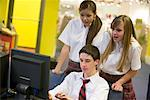 Teenage boy in school uniform using computer while girls watch Stock Photo - Premium Royalty-Free, Artist: Brian Pieters, Code: 638-01584781