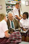 Group of high school students reading in library with teacher Stock Photo - Premium Royalty-Free, Artist: Brian Pieters, Code: 638-01584783