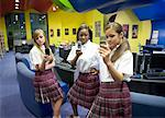 Three teenage students using mobile phone in the library Stock Photo - Premium Royalty-Free, Artist: Brian Pieters, Code: 638-01584821