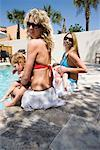 Two young mothers in bikinis with babies at the side of a swimming pool