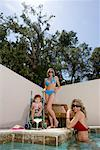 Two attractive young women with baby by swimming pool