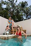 Two attractive young women with babies by swimming pool
