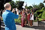 Man Taking Picture of Girls in Prom Dresses