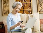 Woman sitting on sofa with laptop and credit card smiling Stock Photo - Premium Royalty-Freenull, Code: 640-01601462